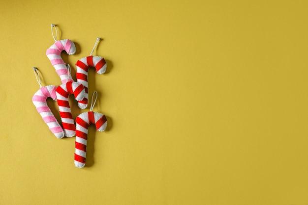 Boże narodzenie ręcznie robione filcowe trzciny cukrowej na żółtym tle z miejsca na kopię, boże narodzenie ręcznie robione ozdoby filcowe