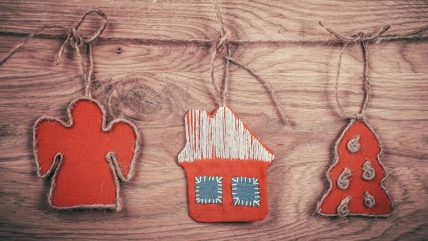 Boże narodzenie ręcznie robione ozdoby przymocowane są do liny na drewnianym tle. miejsce na tekst