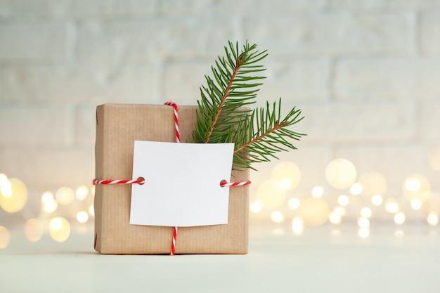 Boże narodzenie ręcznie robione pudełko ozdobione wiecznie zieloną gałązką i pustą pustą kartą upominkową. koncepcja boże narodzenie i nowy rok.