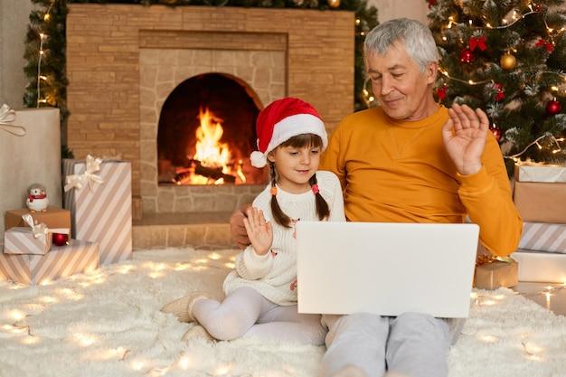 Boże narodzenie rodzina, dziadek i wnuczka na czacie w internecie z laptopa siedząc na podłodze