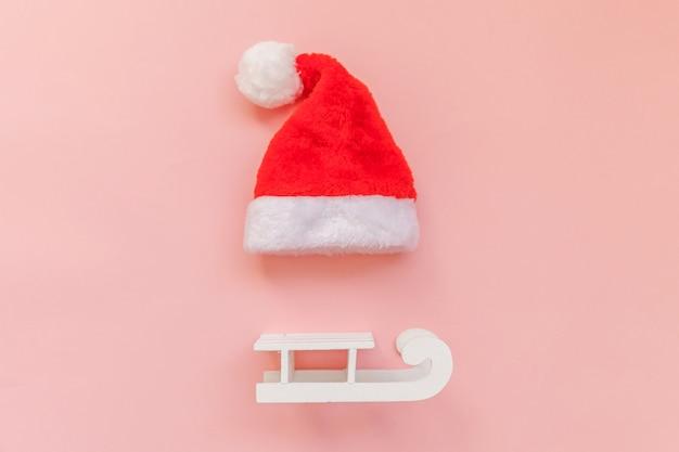 Boże narodzenie santa claus kapelusz sanie na białym tle na różowym pastelowym kolorowym modnym tle