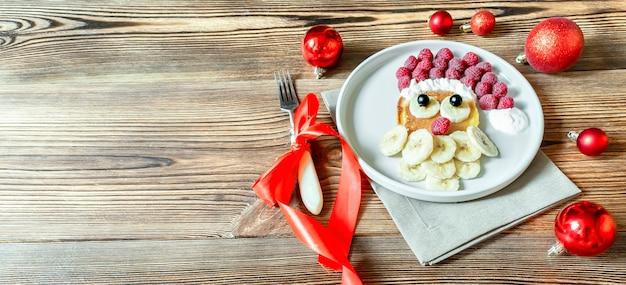 Boże narodzenie santa claus twarz w kształcie naleśnika z jagodami słodkich świeżych malin i bananem na drewnianej płycie tła dla dzieci dzieci śniadanie obiad. świąteczny deser spożywczy dekoracje sylwestrowe, czerwone kulki