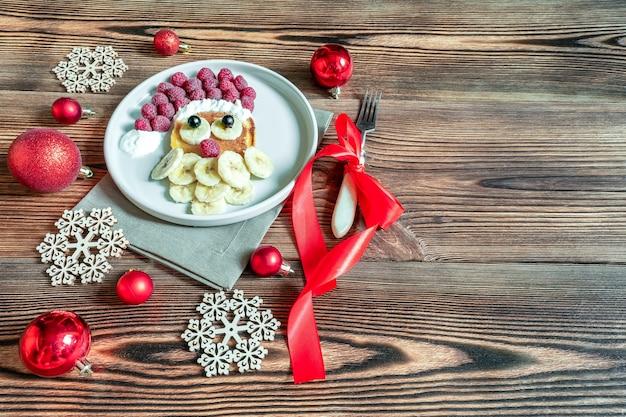 Boże narodzenie santa claus twarz w kształcie naleśnika z jagodami słodkich świeżych malin i bananem na talerzu na drewnianym tle dla dzieci dzieci śniadanie. świąteczny deser spożywczy z dekoracjami noworocznymi, czerwonymi kulkami