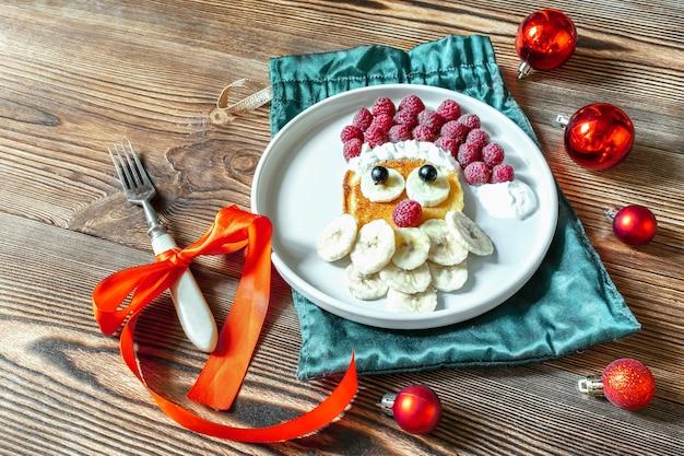 Boże narodzenie santa claus twarz w kształcie naleśnika z jagodami słodkich świeżych malin i bananem na talerzu na drewnianym tle dla dzieci dzieci śniadanie. świąteczny deser spożywczy z dekoracjami sylwestrowymi, czerwone kulki.