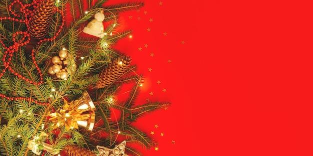 Boże narodzenie ściana z miejsca na kopię. świątecznie zdobione gałęzie świerkowe na czerwonym sztandarem.