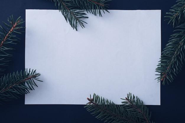 Boże narodzenie sezonowe tło z centralną pustą białą kartką i sosnowymi gałęziami tworzącymi granicę nad granatem z copyspace na świąteczne pozdrowienia