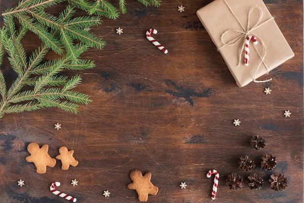 Boże narodzenie skład z prezentem i piernika na drewnianym ciemnym tle. świąteczny tekst świąteczny, szyszki sosnowe, gałęzie jodły na drewnianym biurku, widok płaski i widok z góry, miejsce kopiowania