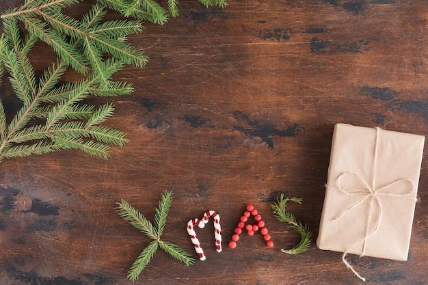 Boże narodzenie skład z prezentem na drewnianym ciemnym tle. świąteczny tekst świąteczny, szyszki sosnowe, gałęzie jodły na drewnianym biurku, widok płaski i widok z góry, miejsce kopiowania