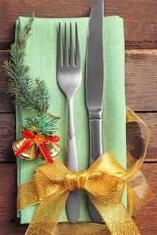 Boże narodzenie służąc sztućce z serwetką na drewnianym stole, z bliska