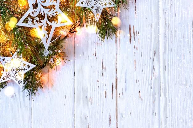 Boże narodzenie śnieżny tło. gałązki jodłowe z płonącą girlandą.