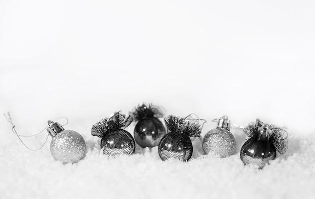 Boże narodzenie srebrne i czarne balony i śnieg na białym tle.