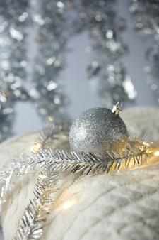 Boże narodzenie. świąteczna zabawka srebrna kulka z iskierkami w wianku na białym wełnianym swetrze z dzianiny.