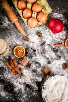 Boże narodzenie, świąteczne gotowanie. składniki, przyprawy, suszone pomarańcze i formy do pieczenia, ozdoby świąteczne (kule, gałąź jodły, szyszki), na czarnym kamiennym stole, widok z góry