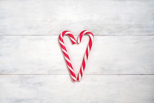 Boże narodzenie świąteczne mieszkanie leżało z cukierkiem. dwie cukierki w kształcie serca