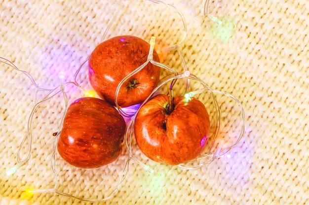 Boże narodzenie światła girlanda i świeże owoce dojrzałe czerwone jabłko na tle dzianiny.