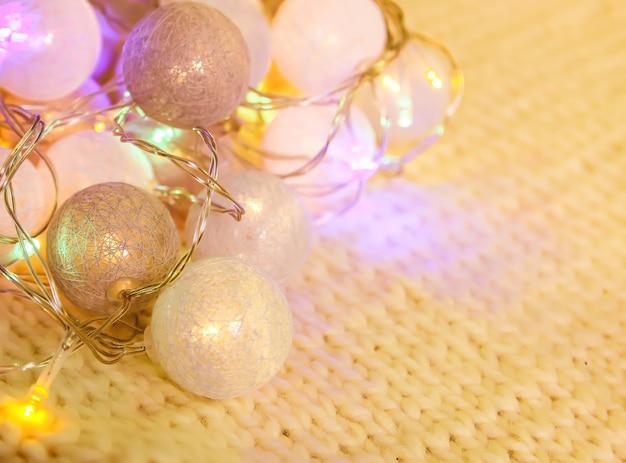 Boże narodzenie światła girlanda z okrągłymi lampionami na tle dzianiny.
