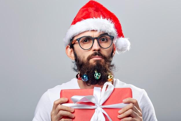 Boże narodzenie, święta, fryzjer i koncepcja stylu - młody przystojny brodaty mikołaj z wieloma małymi bombkami w długiej brodzie.