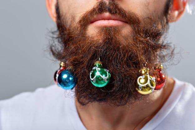 Boże narodzenie, święta, fryzjer i koncepcja stylu - zbliżenie człowieka z wieloma małymi bombkami w długiej brodzie.