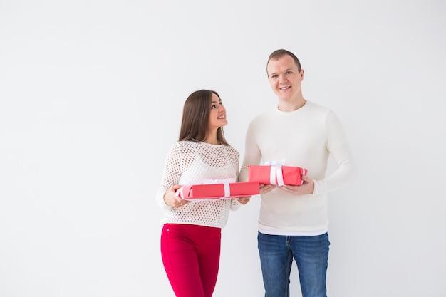 Boże narodzenie, święta, walentynki i urodziny koncepcja - szczęśliwy mężczyzna i kobieta trzyma pudełka z prezentami na białym tle z miejscem na kopię