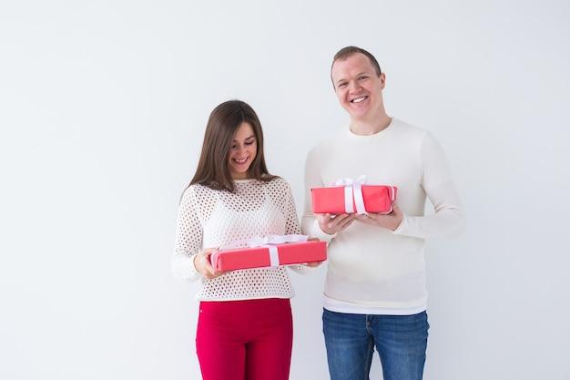 Boże narodzenie, święta, walentynki i urodziny koncepcja - szczęśliwy mężczyzna i kobieta trzyma pudełka z prezentami na białym tle