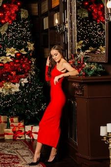 Boże narodzenie, święta, zima, koncepcja szczęścia - uśmiechnięta kobieta w ubraniach mikołaja z wieloma pudełkami prezentowymi
