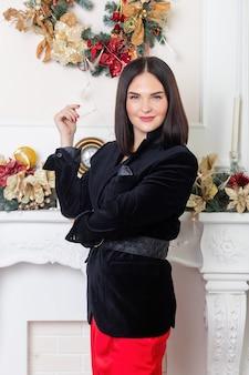 Boże narodzenie święty mikołaj. piękna uśmiechnięta kobieta model. makijaż. elegancka dama w czerwonej spódnicy i czarnej kurtce na tle światła choinki. szczęśliwego nowego roku.