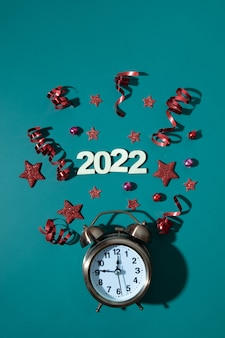 Boże narodzenie szczęśliwego nowego roku płasko leżał z budzikiem, gwiazdami, serpentynami numer 2022 w formacie pionowym