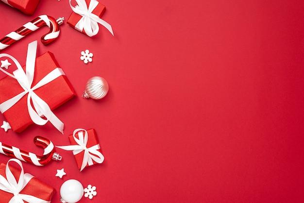 Boże narodzenie tło. czerwone pudełka z ozdób choinkowych na czerwonym tle. widok z góry. leżał płasko. świąteczna kompozycja zimowa
