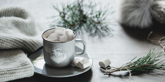 Boże narodzenie tło. filiżanka do kawy z piankami, dzianinowym szalikiem i czapką, kolor szary, gałązki choinki.