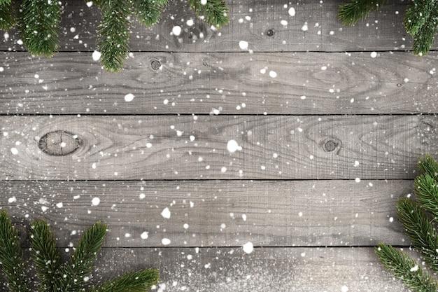 Boże narodzenie tło - gałąź jodła i śnieżynka na rustykalnym stole z drewna. kreatywna kompozycja widoku z góry z obramowaniem i projektem przestrzeni kopii.