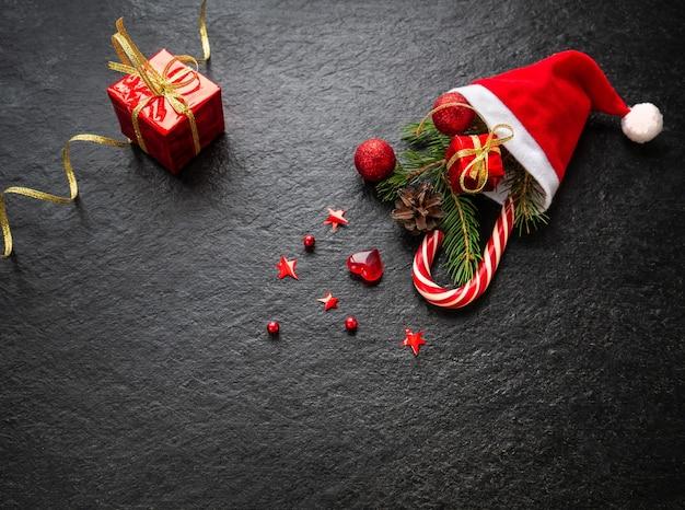 Boże narodzenie tło gałązka jodły ozdoby świąteczne prezent z trzciny karmelowej w kapeluszu świętego mikołaja
