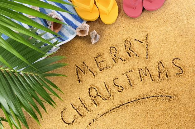 Boże narodzenie tło plaża z ręcznikiem, liści palmowych i klapki