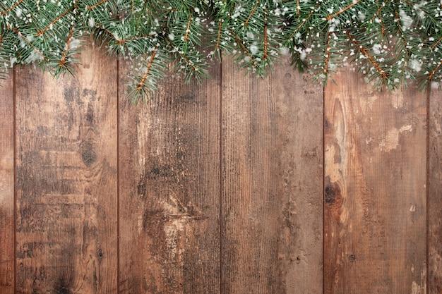 Boże narodzenie tło. stare tło drewna z gałęzi jodłowych i płatki śniegu.