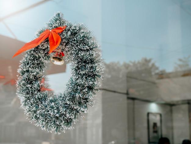 Boże narodzenie tło. świąteczny wieniec z czerwoną wstążką i złotym dzwonkiem wiszącym na czystych szklanych drzwiach przed kawiarnią z miejscem na kopię.