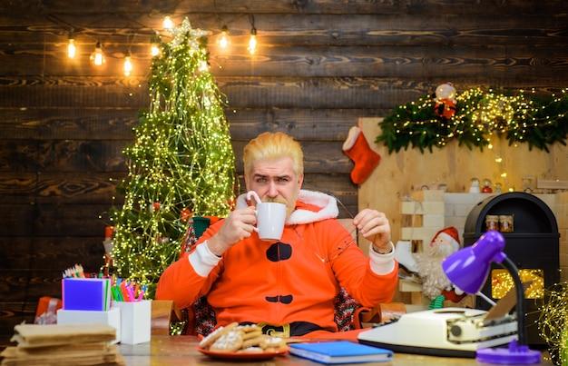 Boże narodzenie tło święty mikołaj pije gorący napój grudzień brodaty święty mikołaj mężczyzna w stroju świętego mikołaja