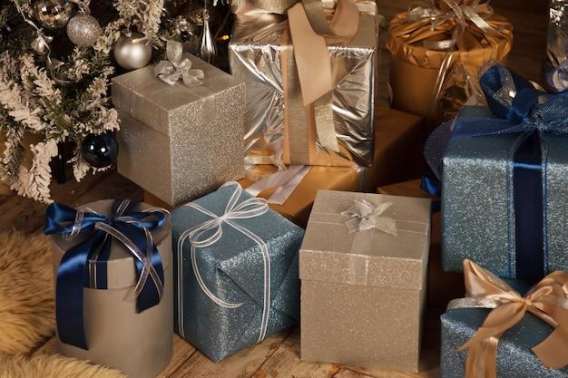 Boże narodzenie tło wakacje pudełek z prezentami nowy rok pod ozdobione choinki. prezenty uroda pakowane ze wstążkami. wystrój pod drzewem we wnętrzu domu. zbliżenie. skopiuj miejsce