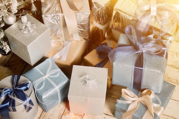 Boże narodzenie tło wakacje pudełek z prezentami nowy rok pod ozdobione choinki w salonie. prezenty z bliska pakowane wstążkami, wystrój pod drzewem we wnętrzu domu. skopiuj miejsce na stronę