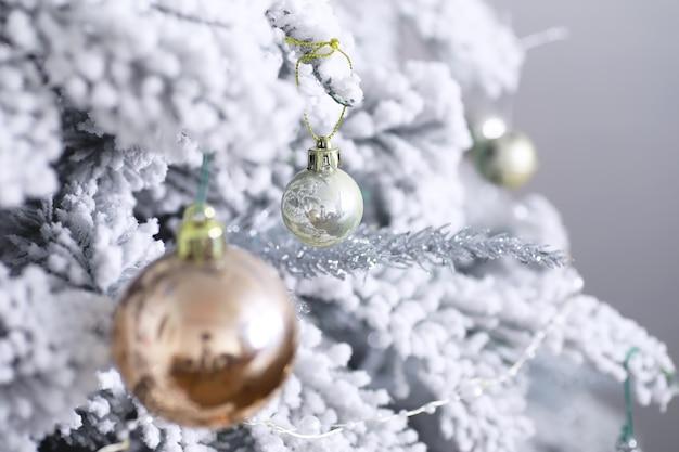Boże narodzenie tło wakacje. srebrna i kolorowa bombka zawieszona na ozdobionym na drzewie z bokeh i śniegiem, kopia przestrzeń.
