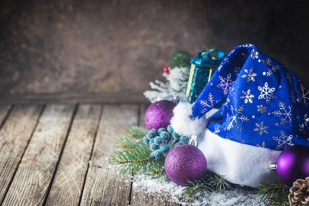 Boże narodzenie tło z bombkami, prezentem, czapką świętego mikołaja i śniegiem na drewnianym tle