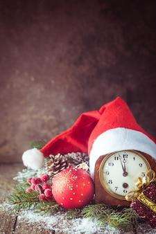 Boże Narodzenie Tło Z Bombkami, Zegarem, Prezentem, Czapką świętego Mikołaja I śniegiem Na Drewnianym Tle Premium Zdjęcia