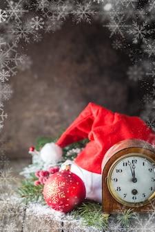 Boże narodzenie tło z bombkami, zegarem, prezentem, czapką świętego mikołaja i śniegiem na drewnianym tle