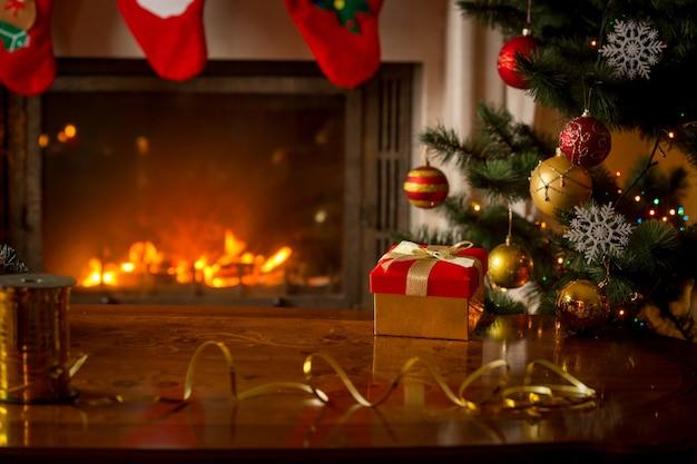 Boże narodzenie tło z czerwonym pudełkiem na drewnianym stole przed płonącym kominkiem i choinką. puste miejsce na tekst