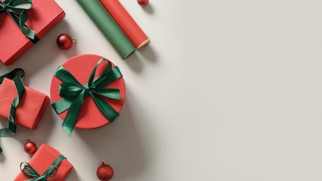 Boże narodzenie tło z czerwonymi i zielonymi pudełkami, rolki papieru na szaro. przygotowanie i pakowanie prezentu dla kobiety na święta. widok z góry z miejscem na kopię.