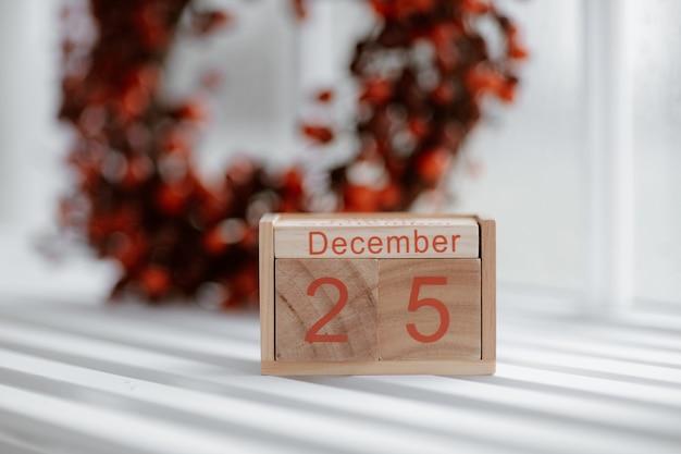 Boże narodzenie tło z drewnianym kalendarzem blokowym z datą 25 grudnia