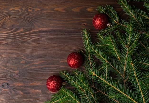 Boże narodzenie tło z gałęzi jodłowych i dekoracje na brązowy stary drewniany stół. miejsce na tekst lub projekt. widok z góry.