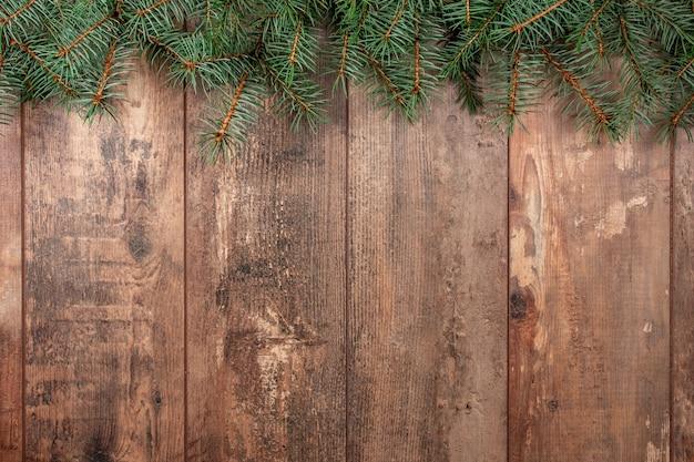 Boże narodzenie tło z jodły. gałęzie choinkowe na drewnianej teksturze gotowe do projektowania