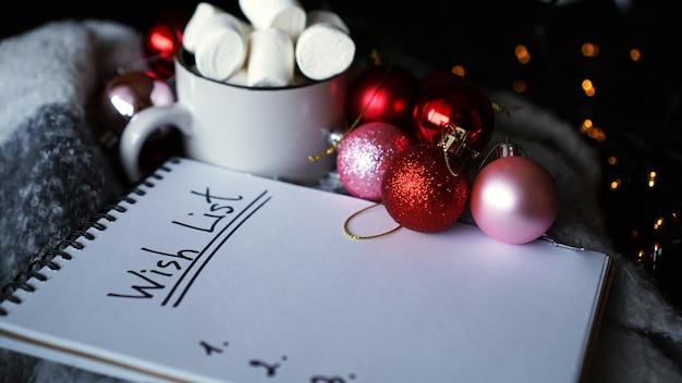 Boże narodzenie tło z listą życzeń, kubek kawy z pianką i bombkami ze światłami na tle