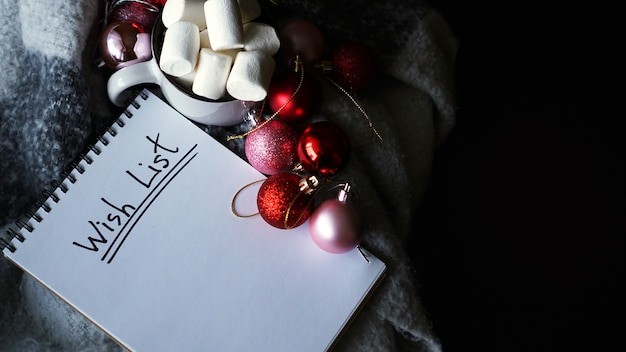 Boże narodzenie tło z listą życzeń, kubek kawy z pianką i bombkami