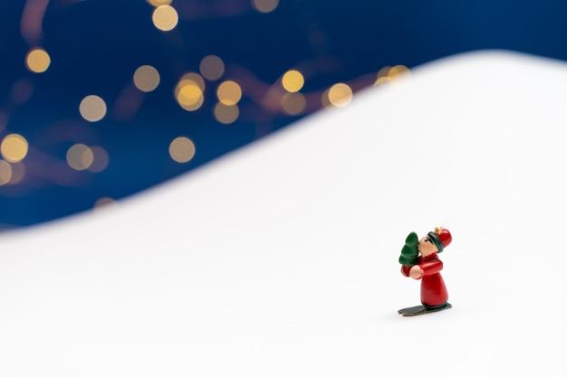 Boże narodzenie tło z małymi postaciami dekoracji drzew pada śnieg w białej górze papieru