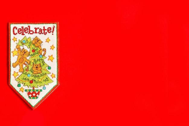Boże narodzenie tło z ozdobnym haftowanym proporcem na czerwonym tle